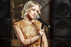 Portret van jonge blondevrouw met microfoon op donkere achtergrond stock fotografie