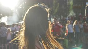 Portret van jonge charmante vrouw status op straat tijdens festival en het golven van haar haar, glimlachend, gelukkig, menigte h stock videobeelden