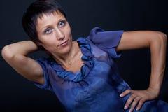 Portret van jonge donkerbruine vrouw in blauw op zwarte Royalty-vrije Stock Afbeeldingen