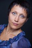Portret van jonge donkerbruine vrouw in blauw op zwarte Royalty-vrije Stock Foto's