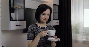 Portret van jonge donkerbruine vrouw die chocolade eten en koffie van kop drinken stock footage
