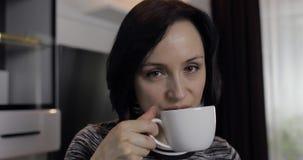 Portret van jonge donkerbruine vrouw die chocolade eten en koffie van kop drinken stock video
