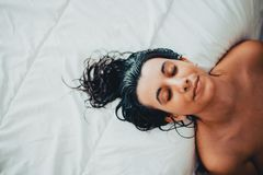 Portret van jonge donkerbruine vrouw die enkel van de douche met nat haar weggaan stock foto