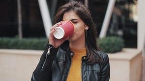 Portret van jonge donkerbruine vrouw het drinken koffie die de camera onderzoeken Het lachen vrolijk portret van succesvol stock video