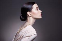 Portret van jonge donkerbruine vrouw tegen een donkere achtergrond Geheimzinnig helder beeld van een vrouw met professionele make Royalty-vrije Stock Foto