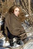 Portret van jonge eenzame meisjeszitting in de winter sneeuw bos Ongelukkige het bevriezen vrouw stock afbeelding