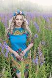 Portret van jonge ernstige vrouw onder de bloemen Stock Fotografie