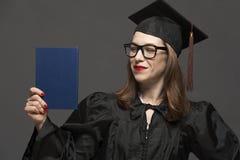 Portret van jonge gediplomeerde volwassen vrouwelijke student in zwarte graduatietoga stock fotografie