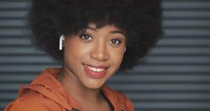 Portret van jonge gelukkige Afrikaanse Amerikaanse vrouw die oortelefoons dragen die de camera onderzoeken Horizontale rolzonnebl stock videobeelden