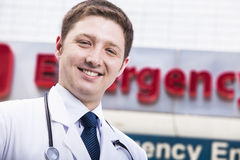 Portret van jonge glimlachende arts buiten het ziekenhuis, het teken van de noodsituatieruimte op de achtergrond royalty-vrije stock afbeeldingen