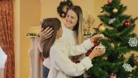 Portret van jonge glimlachende moeder met dochter die Kerstboom verfraaien bij woonkamer stock video