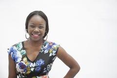 Portret van jonge glimlachende vrouw met hand op heup in traditionele kleding van Afrika, studioschot Stock Afbeeldingen