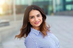 Portret van jonge glimlachende vrouw in openlucht met sunligthgloed stock foto