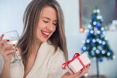 Portret van jonge glimlachende vrouw in verfraaide woonkamer met giften en Kerstboom Stock Fotografie