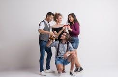 Portret van jonge groep vrienden die zich in een studio bevinden, houdend flessen en glazen royalty-vrije stock afbeelding