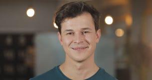 Portret van jonge het glimlachen succesvolle zakenman status in modern bureau Sluit omhoog stock video
