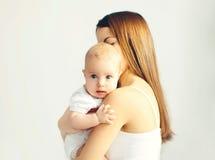 Portret van jonge houdende van moeder die haar zuigeling koesteren royalty-vrije stock afbeelding