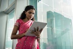 Portret van jonge Indische vrouw die een tabletpc in openlucht met behulp van royalty-vrije stock afbeelding