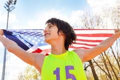 Portret van jonge kampioen die Amerikaanse vlag golven stock foto