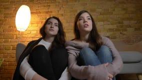 Portret van jonge Kaukasische meisjes die samen op de de vloer en het letten op film met positief vermaak in comfortabel huis zit stock videobeelden