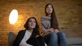 Portret van jonge Kaukasische meisjes samen en het letten op film die met positief vermaak in comfortabele huisatmosfeer zitten stock footage