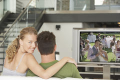Portret van jonge Kaukasische vrouw met man het letten op film op televisie in woonkamer stock foto's