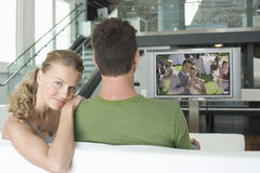 Portret van jonge Kaukasische vrouw met man het letten op film op televisie in woonkamer royalty-vrije stock foto's