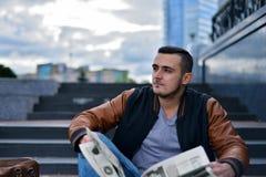 Portret van jonge kerel in de lezingskrant van het leerjasje in de stad royalty-vrije stock fotografie