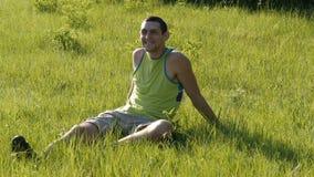 Portret van jonge knappe vrolijke mensenzitting op het gras in aard in de zomer op bosachtergrond en rond het kijken stock footage
