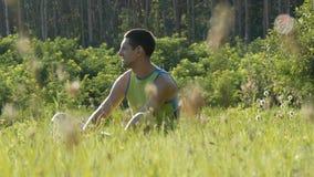 Portret van jonge knappe vrolijke mensenzitting op het gras in aard in de zomer op bosachtergrond en rond het kijken stock videobeelden