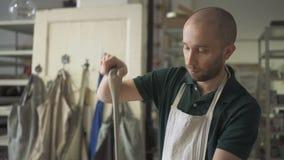 Portret van jonge mannelijke ceramist, die het werk van kleifto in zijn heldere studio voorbereidt stock footage