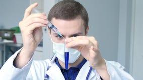 Portret van jonge mannelijke Kaukasische arts die een vloeistof van een spuit gieten aan een buis stock footage