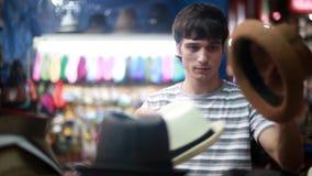 Portret van jonge mannelijke koper in de straatwinkel die nieuwe hoed uitproberen en spiegel bekijken 1920x1080 stock footage