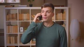 Portret van jonge mannelijke student die belangrijke voicecall die op smartphone hebben aandachtig bij bibliotheek zijn stock video