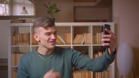 Portret van jonge mannelijke student die videovraag met vriend die op smartphone hebben blij bij bibliotheek zijn stock footage