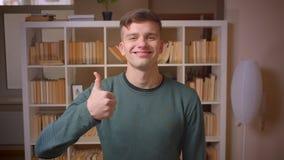 Portret van jonge mannelijke studentengebaren duim-omhoog om overeenkomst en goedkeuring bij bibliotheek te tonen stock video