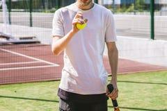 Portret van jonge mannelijke tennisspeler op hof op een zonnige dag stock foto