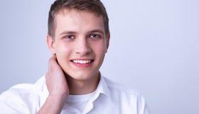 Portret van jonge mens het glimlachen zitting op grijze achtergrond Royalty-vrije Stock Foto