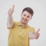 Portret van jonge mens het glimlachen zitting op grijze achtergrond Royalty-vrije Stock Afbeelding