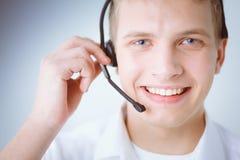 Portret van jonge mens het glimlachen zitting op grijze achtergrond Portret van de jonge mens Stock Foto's