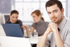 Portret van jonge mensenzitting bij vergaderingslijst Stock Foto's