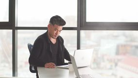 Portret van jonge mensenzitting bij zijn bureau in het bureau stock video