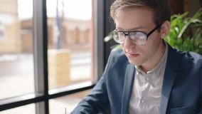 Portret van jonge mensenzitting in de koffie dichtbij venster met stadsmening stock video