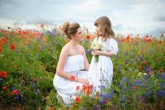 Portret van jonge moeder en dochter met wilde bloemen onder Th Royalty-vrije Stock Afbeeldingen