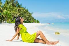 Portret van jonge mooie Aziatische meisjeszitting op het strand en omhoog het kijken Stock Foto