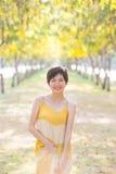 Portret van jonge mooie Aziatische vrouw die gele lang dragen dres Stock Afbeelding