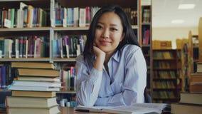 Portret van jonge mooie Aziatische vrouwelijke studentenzitting bij lijst met stapels van handboeken in bibliotheek die camera be stock footage