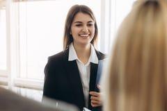 Portret van jonge mooie bedrijfsvrouw in het bureau die nieuwe arbeiders ontmoeten stock foto's