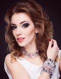 Portret van jonge mooie donkerbruine vrouw in juwelen die o bevinden zich Stock Foto's