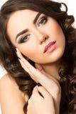 Portret van jonge mooie donkerbruine vrouw wat betreft haar gezicht Stock Afbeelding